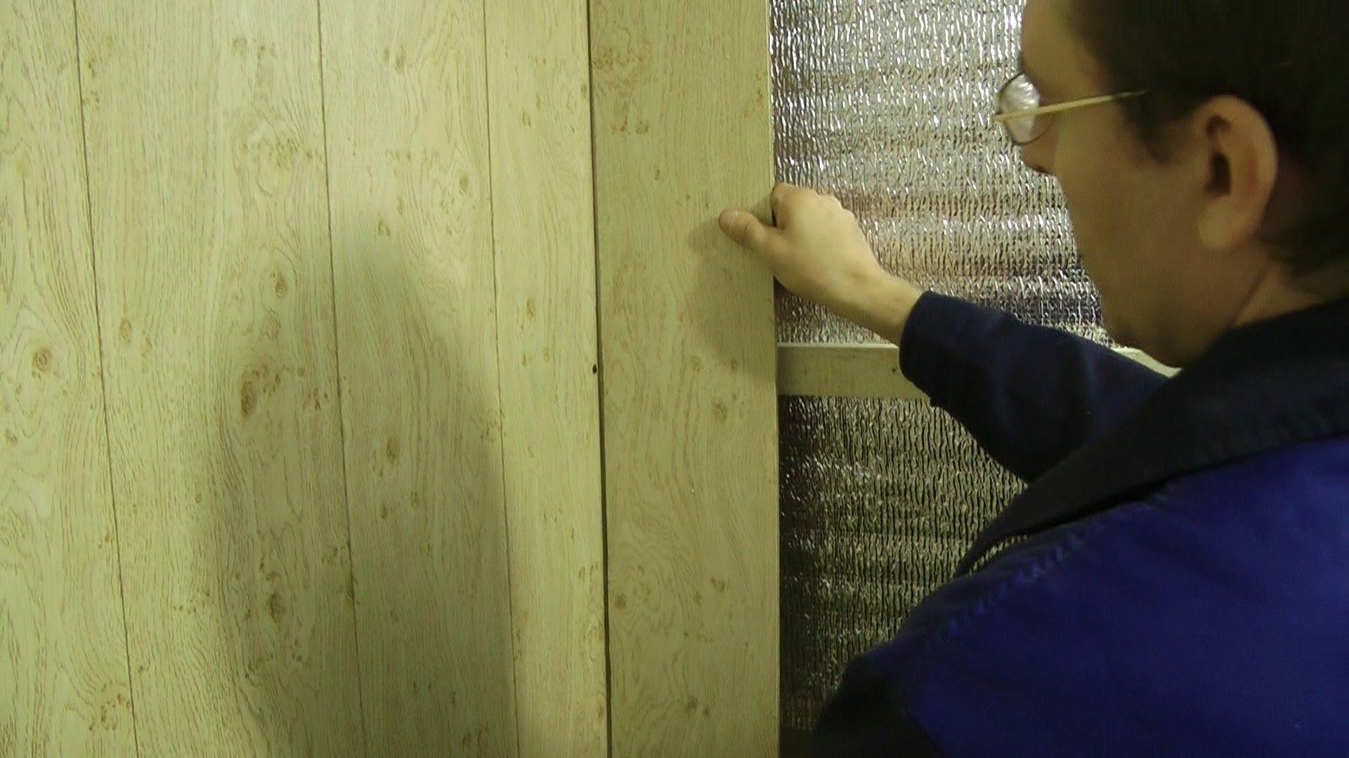 El forro debajo del panel de plástico en la pared del baño. Método n ...